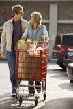 Couple leaving supermarket, woman pushing shopping trolley in car park, smiling, front view Stock Photo