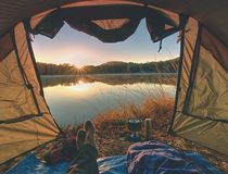 Couple legs rest in tent at lake. Hiker enjoy view stock image