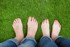 Couple legs standing together on grass Royalty Free Stock Photo