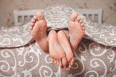 Couple legs stick out from under a blanket Royalty Free Stock Image
