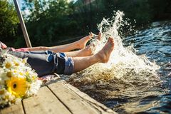 Couple legs in the water splashing Stock Images
