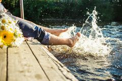 Couple legs in the water splashing with bouquet of  flowers. Summer joy Royalty Free Stock Photo