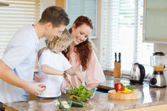 Couple letting their child stir the salad Stock Image