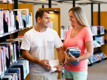 Couple in library with books Stock Photos