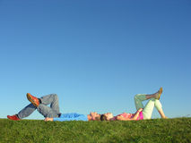 Couple lie on blue sky. And green grass stock photography