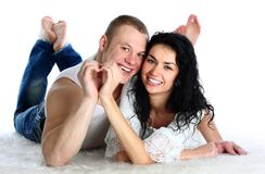 Couple lie on the floor nd making heart by hands Stock Photos