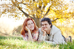 Couple lie at green grass in the park. Outdoo shot Royalty Free Stock Image