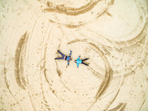 Couple lie on a sandy ground Stock Image