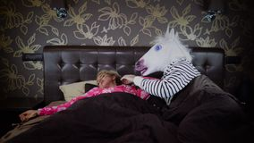 Couple lies in bed at stylish bedroom. Funny couple lies in bed at stylish bedroom. Unusual man in comical unicorn mask wakes up girlfriend and scares her. Young stock video footage