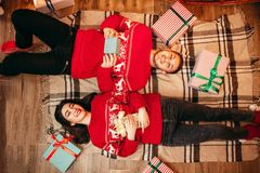Couple lies on the floor, top view, christmas. Happy love couple with gifts lies on the floor, top view, christmas holidays. Xmas celebration, cheerful men and Stock Image