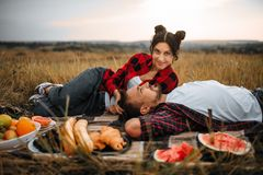 Couple lies on plaid, fruit picnic in summer field royalty free stock photos