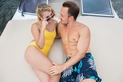 The couple lies on the stern of the yacht and look at each other stock photos