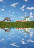 Couple lies under clouds Stock Images