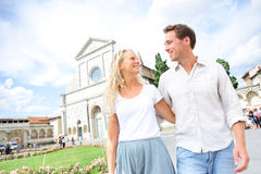 Couple lifestyle Europe travel in Florence, Italy. Happy young couple on romantic travel vacation walking together in love on Santa Maria Novella Square in royalty free stock images