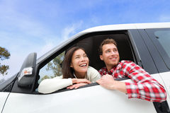 Couple lifestyle in new car looking out window. Driving young men and women enjoying view on travel road trip in new car. Beautiful young multiracial young Royalty Free Stock Photo