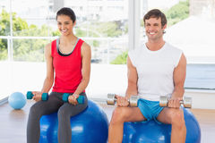 Couple lifting dumbbells while sitting on fitness balls in gym Royalty Free Stock Image