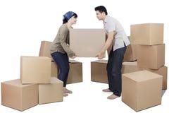 Couple lifting heavy cardboard Royalty Free Stock Image