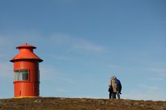 Couple and lighthouse. Elderly couple walking towards shabby lighthouse Stock Images