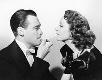 Couple lighting two cigarettes at once with a cigarette lighter Royalty Free Stock Photography