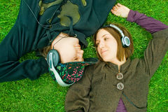 Couple listening music. Young couple listening music on grass Stock Photo