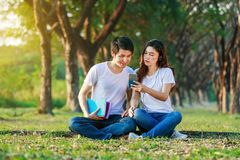 Couple listening music from mobile with headphone in the park. Young couple listening music from mobile with headphone in the park Royalty Free Stock Images
