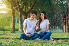 Couple listening music from mobile with headphone in the park. Young couple listening music from mobile with headphone in the park Royalty Free Stock Image