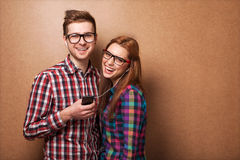 Couple listening music. Young couple listening music together. Hipster style Royalty Free Stock Photography