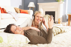 Couple Listening To MP3 Player Laying On Rug Stock Photo
