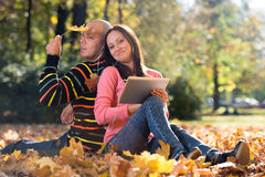 Couple Listening To Music On Autumn Leaves Stock Photo