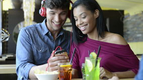 Couple listening to music at bar. Closeup shot of young couple listening to music with mobile phone at coffee bar. Young man and african woman looking at stock video footage