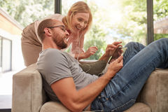 Couple listening to music on a tablet and sharing earphones Stock Photo