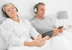 Couple listening to music on their smartphones Stock Photos