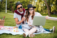 Couple listening to music and using laptop outdoors Stock Images