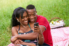 Couple Listening To Music And Watching Video On Mobile Phone Royalty Free Stock Photo