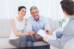 Couple listening to salesman holding contract. At home on couch stock photos