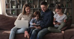 Couple and little children relax on couch using diverse devices