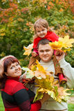 Couple and little girl collect maple leafs In park Stock Images