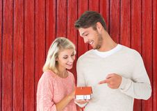 couple with little house in the hands with red wood background Stock Photo
