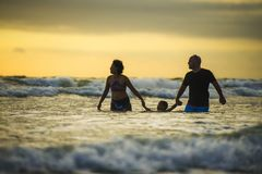 Couple and little son walking relaxed on sunset beach enjoying romantic Summer holidays family trip the parents holding the child royalty free stock photography