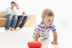 Couple in living room with baby stock images