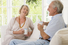 Couple in living room with coffee smiling Royalty Free Stock Image