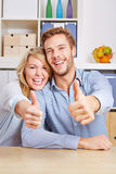 Couple in living room holding Stock Photo