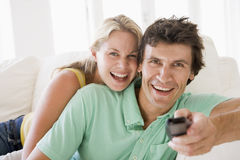 Couple in living room holding remote control Royalty Free Stock Images