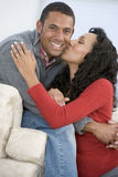 Couple in living room kissing and smiling Royalty Free Stock Photos