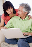 Couple in living room with laptop smiling Stock Photo