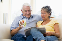 Couple in living room reading newspaper Royalty Free Stock Image