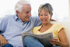Couple in living room reading newspaper smiling Royalty Free Stock Photos