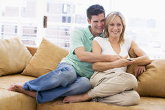 Couple in living room with remote control Stock Images