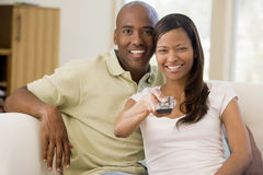 Couple in living room with remote control Royalty Free Stock Image