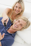 Couple in living room with remote control smiling Royalty Free Stock Photo